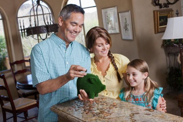Family saving money in green piggy bank